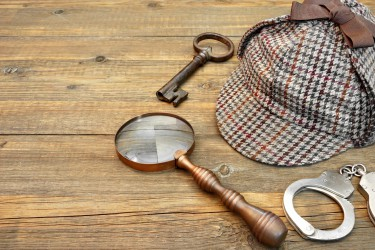 Sherlock Holmes Cap famous as Deerstalker, Old Key, Real Handcuffs and Vintage Magnifying Glass on Grunge Wooden Table