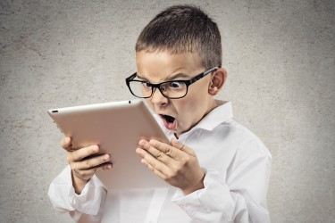 Closeup portrait child, shocked, surprised, funny looking boy with glasses using, holding laptop, pad computer isolated grey, black background. Human face expressions, emotions, reaction body language
