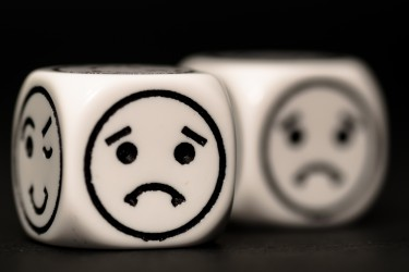 emoticon dice with sad expression sketch on black background - stock photo