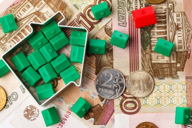 Close up of small toy houses and russian rubles